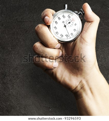 hand holding a stopwatch against a grunge background