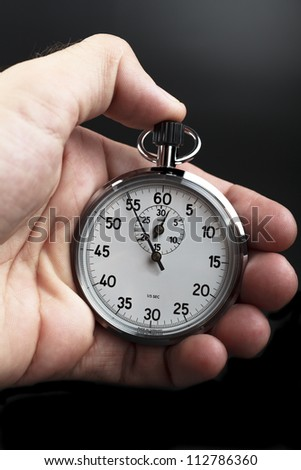 Hand holding a stopwatch on black background - stock photo