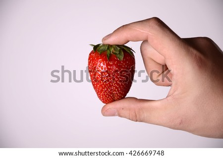 hand holding a strawberry
