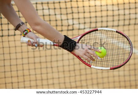 Hand holding a tennis ball seen through a racket's string