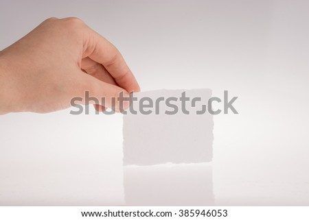 Hand holding a torn piece of paper on a white background