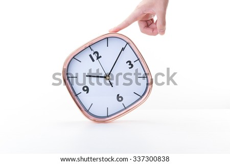 Hand holding a wall clock, white background - stock photo