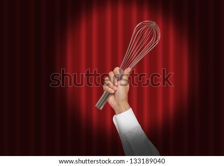 Hand holding a whisk under a spot light