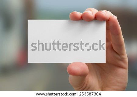 Hand holding a white business card on blurred background  - stock photo