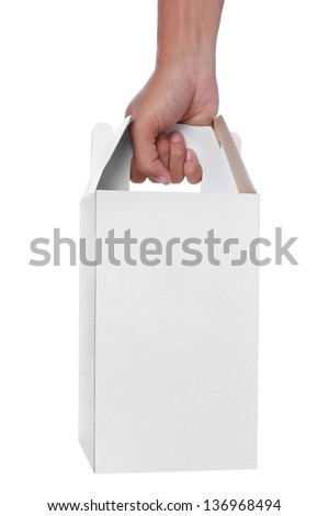 hand holding a white empty box with handle isolated over a white background - stock photo