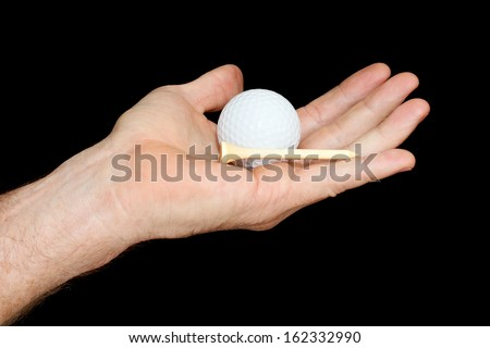 Hand Holding a White Golf Ball and Wooden Tee isolated on black