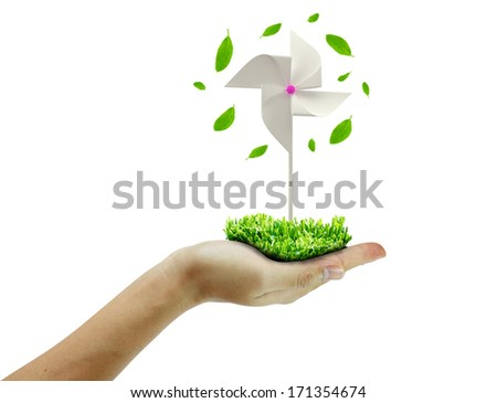 hand holding a white pinwheel and green leafs  - stock photo