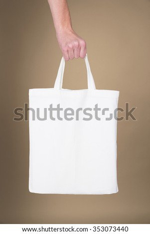 Hand holding a white textile bag over brown background -  usable as a mockup for your message - stock photo