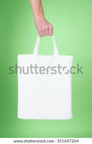 Hand holding a white textile bag over green background -  usable as a mockup for your ecological message - stock photo