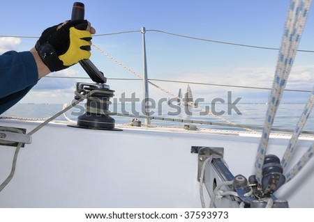 Hand holding a winch handle with sailboats in background