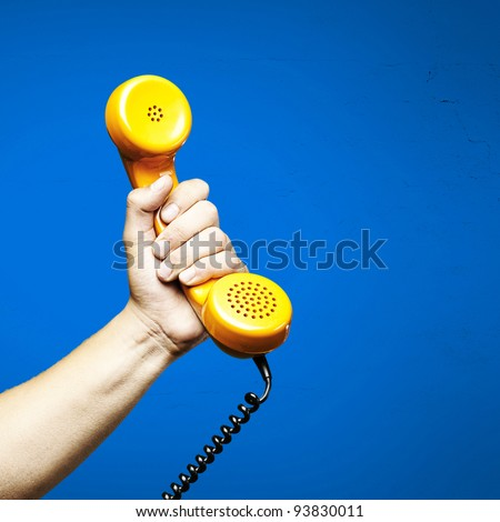 hand holding a yellow vintage telephone over a blue background - stock photo
