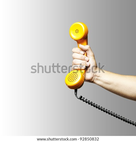 hand holding a yellow vintage telephone over grey background