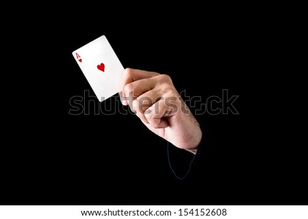Hand holding ace of hearts card on black background