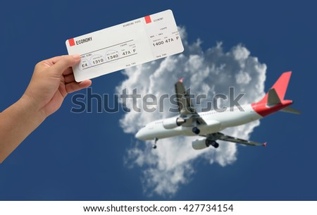 hand holding Airline boarding pass ticket on plane was landing and sky-clouds background.
