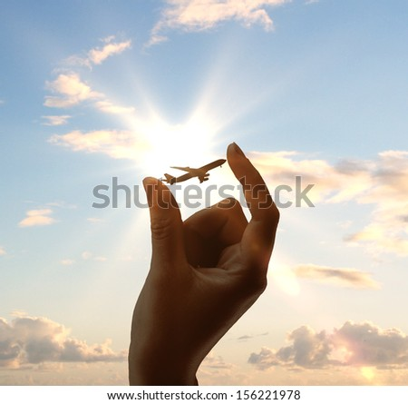 hand holding airplane on sky background - stock photo