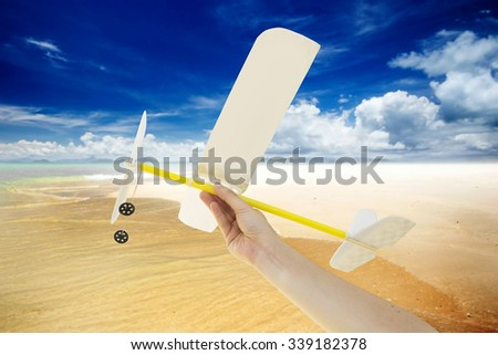 Hand holding airplane plane on beach and blue sky many cloud background - stock photo
