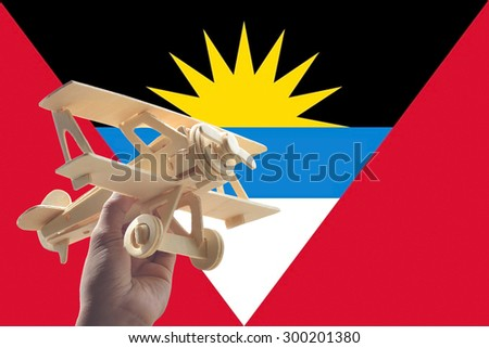 Hand holding airplane plane over Antigua Barbuda flag, travel concept - stock photo