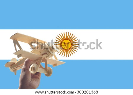 Hand holding airplane plane over Argentina flag, travel concept - stock photo