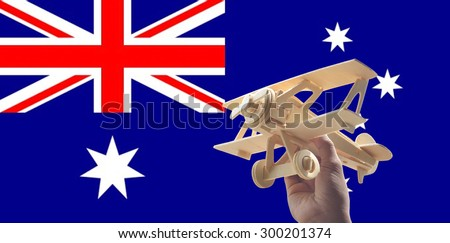 Hand holding airplane plane over Australia flag, travel concept - stock photo