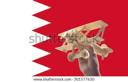 Hand holding airplane plane over Bahrain flag, travel concept - stock photo