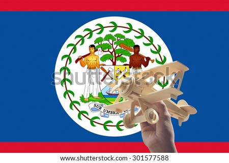 Hand holding airplane plane over Belize flag, travel concept - stock photo