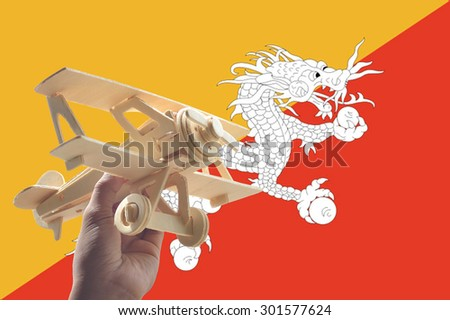 Hand holding airplane plane over Bhutan flag, travel concept - stock photo