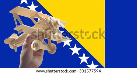 Hand holding airplane plane over Bosnia Herzegovina flag, travel concept - stock photo