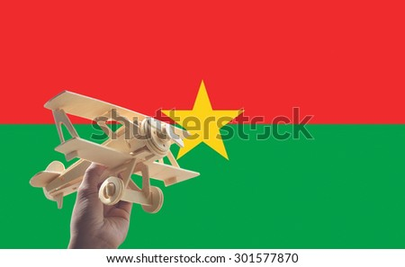 Hand holding airplane plane over Burkina Faso flag, travel concept - stock photo