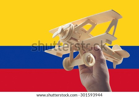 Hand holding airplane plane over Colombia flag, travel concept - stock photo