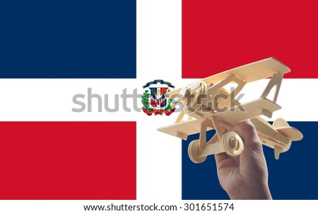 Hand holding airplane plane over Dominican Republic flag, travel concept - stock photo
