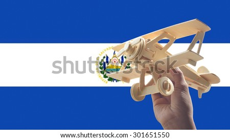 Hand holding airplane plane over El Salvador flag, travel concept - stock photo