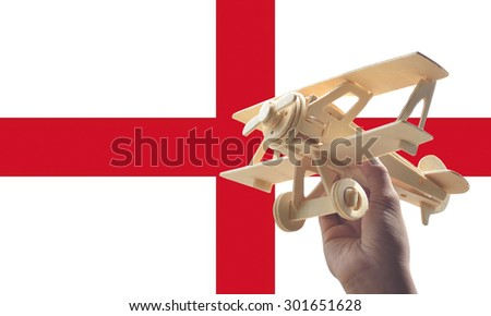 Hand holding airplane plane over England flag, travel concept - stock photo