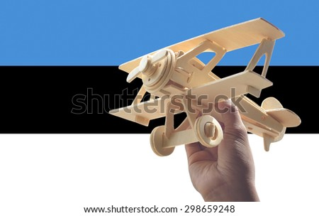 Hand holding airplane plane over Estonia flag, travel concept - stock photo