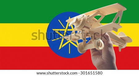 Hand holding airplane plane over Ethiopia flag, travel concept - stock photo