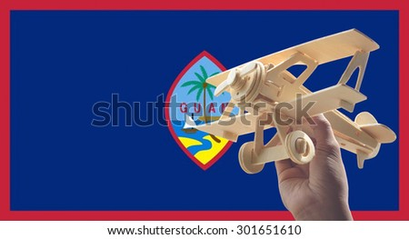Hand holding airplane plane over Guam flag, travel concept - stock photo