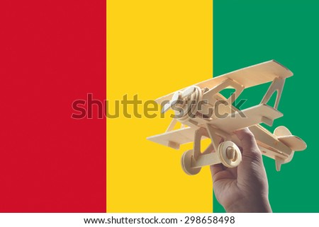 Hand holding airplane plane over Guinea flag, travel concept - stock photo