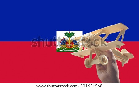 Hand holding airplane plane over Haiti flag, travel concept - stock photo