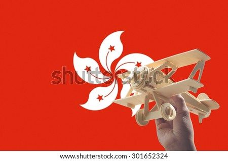 Hand holding airplane plane over Hong Kong flag, travel concept - stock photo
