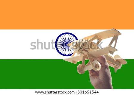 Hand holding airplane plane over India flag, travel concept - stock photo
