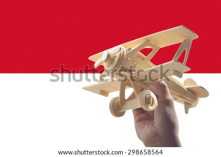 Hand holding airplane plane over Indonesia flag, travel concept - stock photo