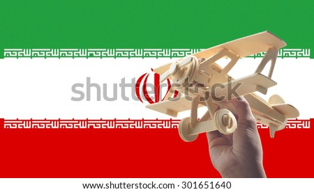 Hand holding airplane plane over Iran flag, travel concept - stock photo