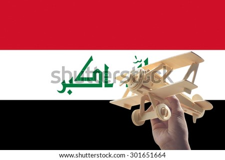 Hand holding airplane plane over Iraq flag, travel concept - stock photo