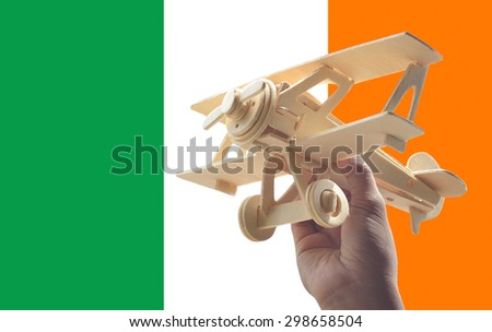 Hand holding airplane plane over Ireland flag, travel concept - stock photo