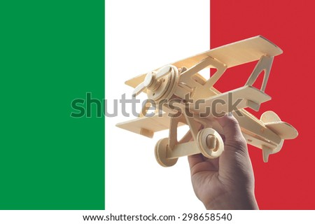 Hand holding airplane plane over Italy flag, travel concept - stock photo