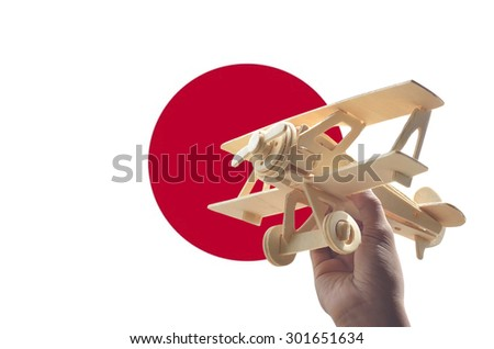 Hand holding airplane plane over Japan flag, travel concept - stock photo