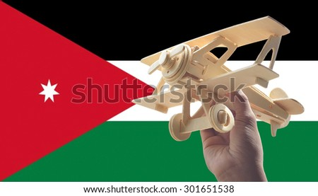 Hand holding airplane plane over Jordan flag, travel concept - stock photo