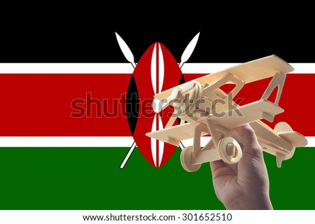 Hand holding airplane plane over Kenya flag, travel concept - stock photo