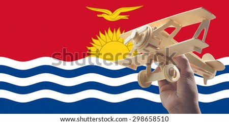 Hand holding airplane plane over Kiribati flag, travel concept - stock photo