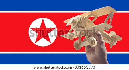 Hand holding airplane plane over North Korea flag, travel concept - stock photo