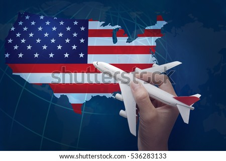 hand holding airplane with map of United States.